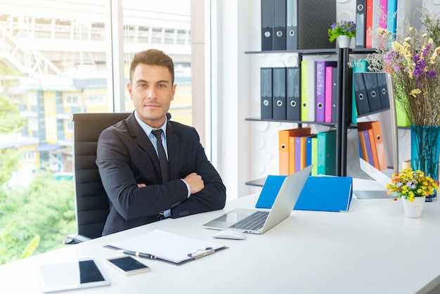 Portrait of handsome businessman sitting with arm-crossed in office. Premium Photo