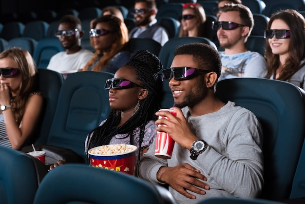 Portrait of a handsome cheerful african man smiling while watching a 3d movie with his girlfriend at the movie theatre Premium Photo