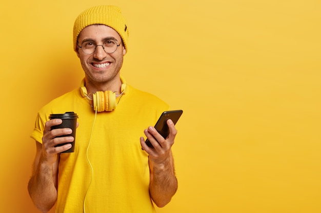 Ritratto di bel giovane allegro con l'espressione del viso soddisfatto, tiene il telefono cellulare, invia messaggi di testo agli amici, beve caffè da asporto, indossa occhiali, vestito giallo con le cuffie Foto Gratuite