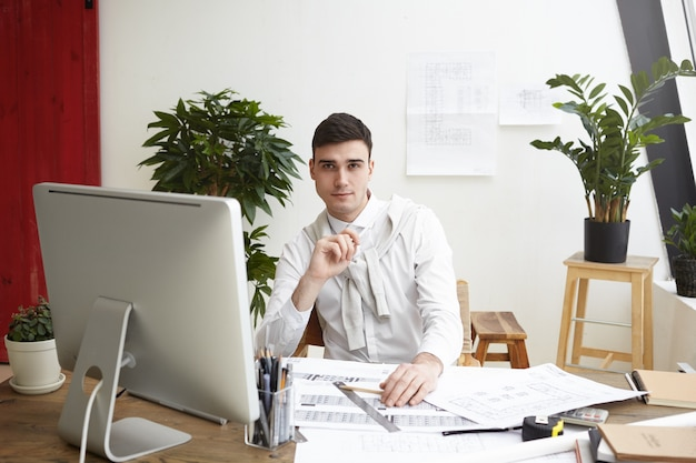 Portrait of handsome confident young male engineer making drawings of residential housing project or commercial building, sitting at his desk with blueprints, computer and engineering tools Free Photo