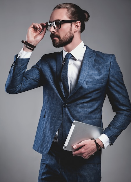 Portrait of handsome fashion businessman model dressed in elegant blue suit with glasses Free Photo