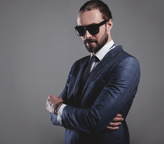Portrait of handsome fashion businessman  model dressed in elegant blue suit with sunglasses Free Photo