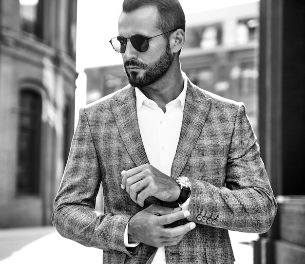 Portrait of handsome fashion businessman model dressed in elegant checkered suit posing on street Free Photo