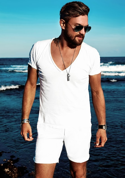 Portrait of handsome fashion man model wearing white clothes posing on blue sea Free Photo