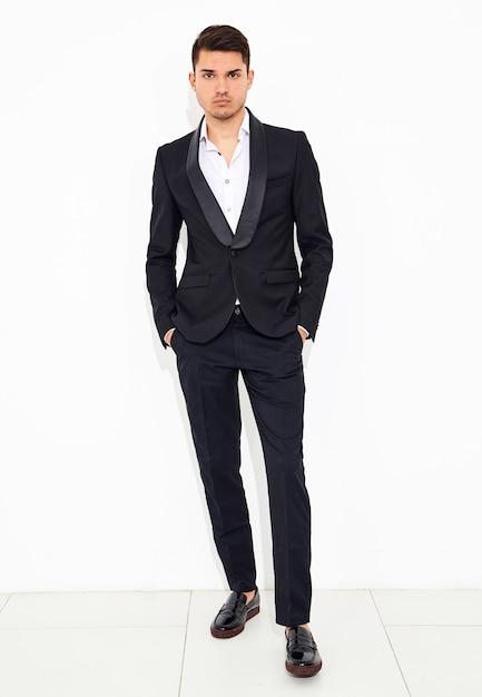 Portrait of handsome fashion stylish businessman model dressed in elegant black classic suit posing. metrosexual Free Photo
