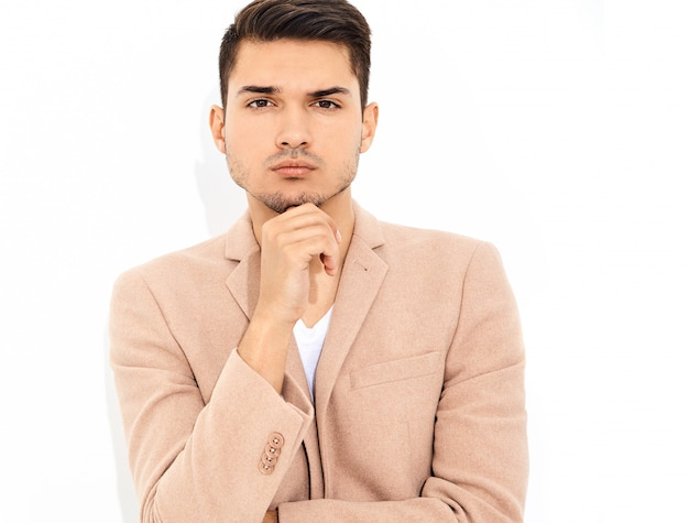 Portrait of handsome fashion stylish businessman model dressed in elegant light pink suit posing. metrosexual Free Photo