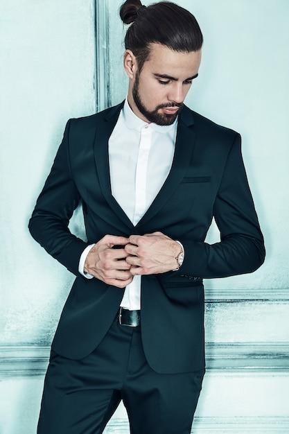 Portrait of handsome fashion stylish hipster businessman model dressed in elegant black suit Free Photo