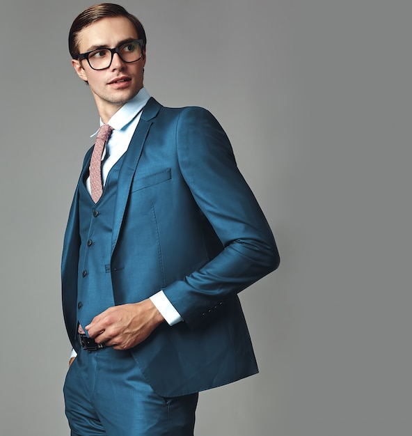 Portrait of handsome fashion stylish hipster businessman model dressed in elegant blue suit  posing on gray background in studio in glasses Free Photo