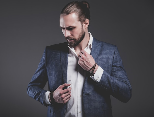 Portrait of handsome fashion stylish hipster businessman model dressed in elegant blue suit posing on gray Free Photo