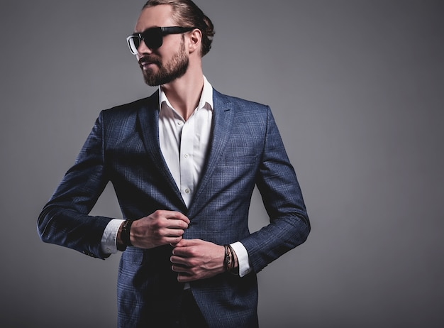 Portrait of handsome fashion stylish hipster businessman model dressed in elegant blue suit in sunglasses posing on gray Free Photo
