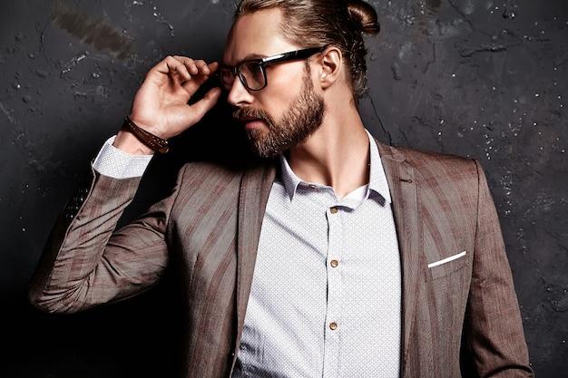 Ritratto del modello di uomo d'affari alla moda hipster alla moda bello vestito in elegante abito marrone con gli occhiali vicino al muro scuro Foto Gratuite