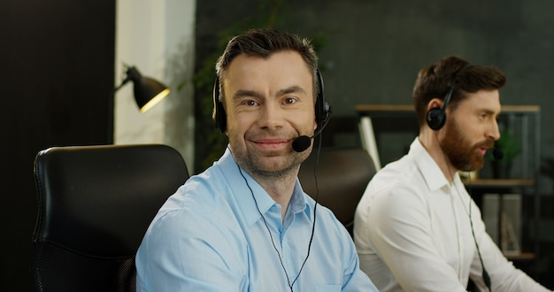 Portrait of handsome happy man in headset working at computer in call center. male operators co-workers of support in office. Premium Photo