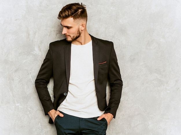 Portrait of handsome hipster   businessman model wearing casual black suit. Free Photo