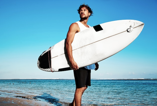 Portrait of handsome hipster sunbathed fashion man model surfer wearing casual clothes going with surfboard on blue ocean and sky Free Photo