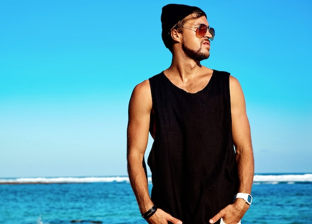 Portrait of handsome hipster sunbathed fashion man model wearing casual clothes in black t-shirt and sunglasses posing Free Photo