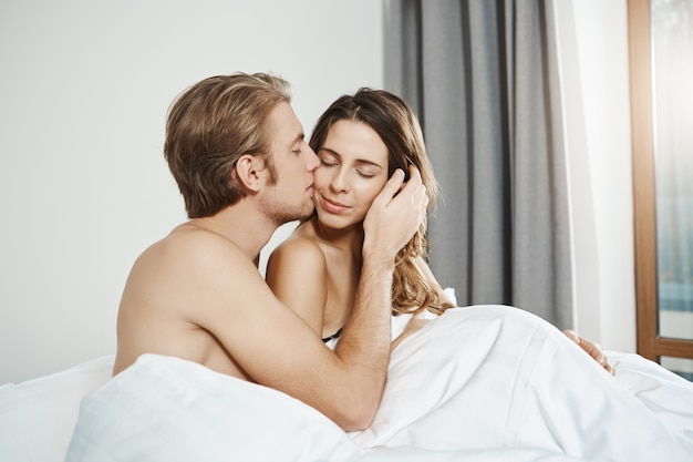 Portrait of handsome husband gently kissing his attractive wife in cheek while lying together in bed in daytime. couple cuddling while in bedroom, having forgot about everything that surround them Free Photo