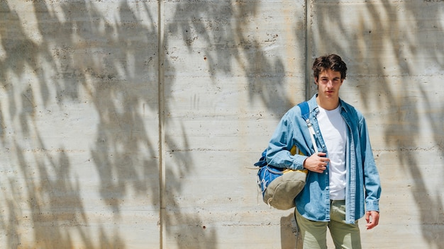 Portrait of handsome man carrying bag looking at camera standing against concrete wall Free Photo