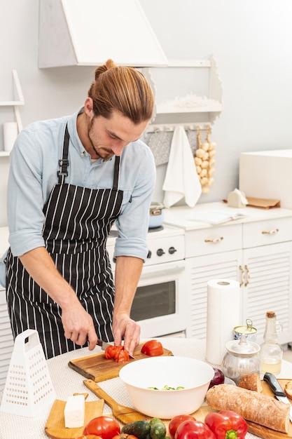 Portrait of handsome man cutting tomato Free Photo