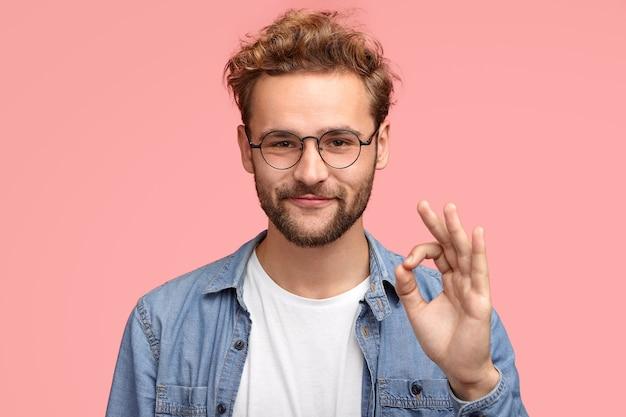 Il ritratto di un bell'uomo ha la barba incolta, fa un segno ok, è d'accordo o gli piace qualcosa ha un'espressione gioiosa, posa contro il muro rosa, dimostra che tutto va secondo i piani. concetto di linguaggio del corpo Foto Gratuite