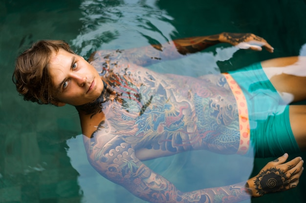 Portrait of a handsome man in tattoos at the pool Premium Photo