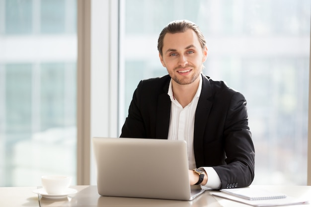 Portrait of handsome smiling businessman at work in office. Free Photo