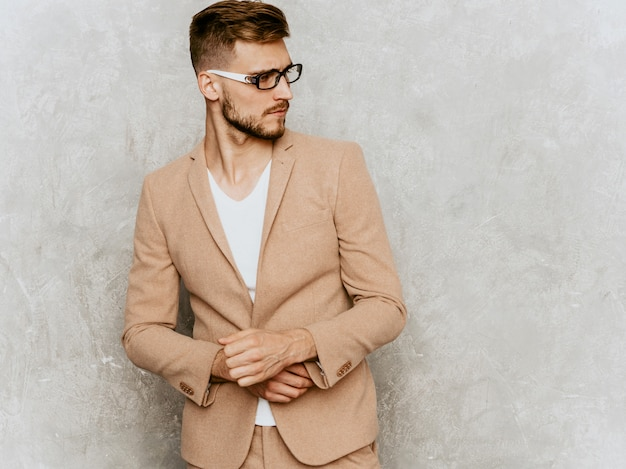 Portrait of handsome smiling hipster   businessman model wearing casual beige suit Free Photo