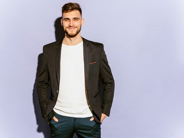 Portrait of handsome smiling hipster  businessman model wearing casual black suit. Free Photo