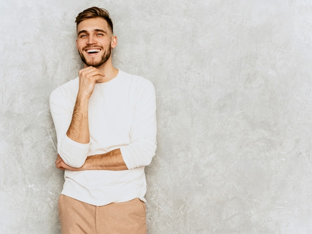 Portrait of handsome smiling hipster   businessman model wearing casual summer white clothes. Free Photo