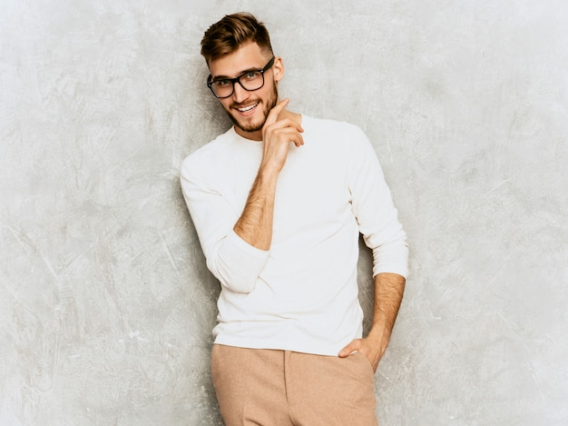 Portrait of handsome smiling hipster   businessman model wearing casual summer white clothes Free Photo