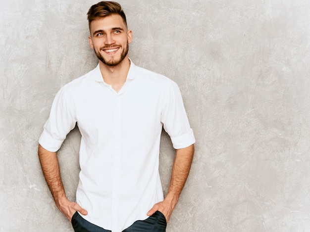 Portrait of handsome smiling hipster  businessman model wearing casual summer white shirt. . hands in pockets Free Photo