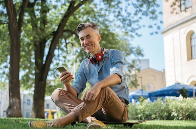 Portrait of handsome smiling man holding mobile phone Premium Photo