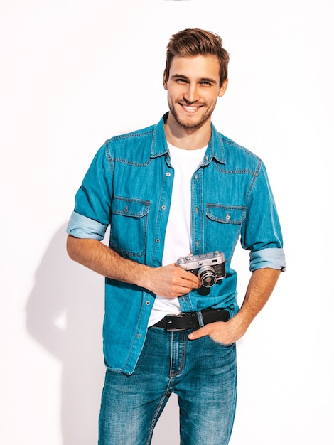 Portrait of handsome smiling man wearing summer jeans clothes. model male taking picture on old vintage photo camera. Free Photo