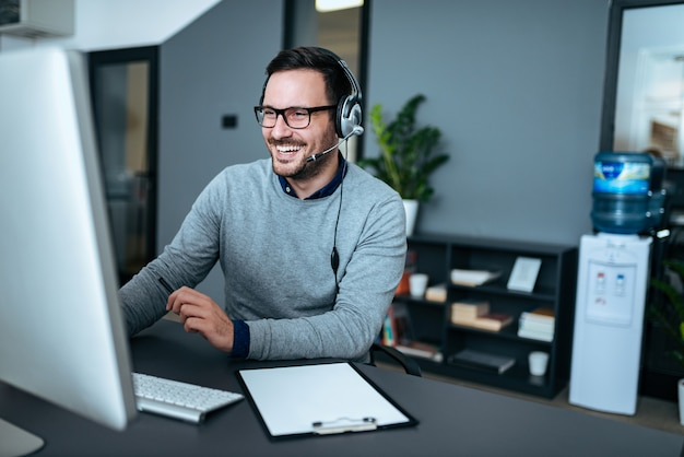Portrait of a handsome smiling man with headset working on the computer. Premium Photo