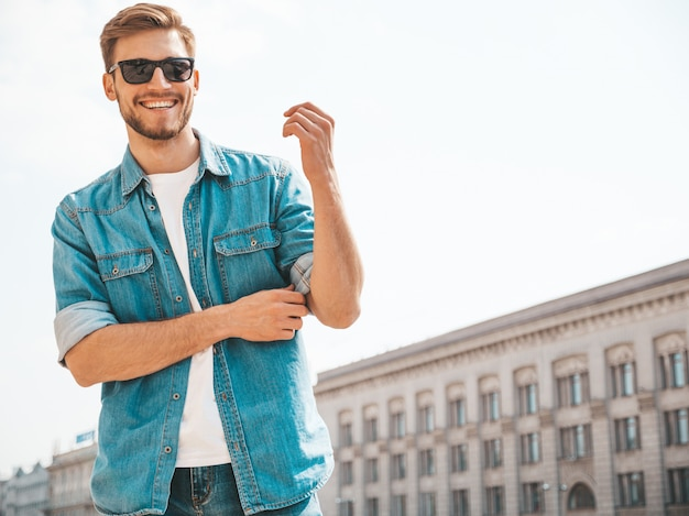 Portrait of handsome smiling stylish hipster lumbersexual businessman model. man dressed in jeans jacket clothes. Free Photo