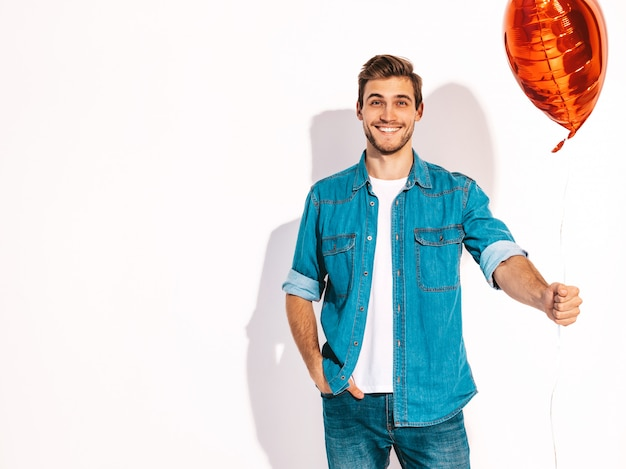 Portrait of handsome smiling stylish man model dressed in jeans clothes. fashion man holding heart shaped balloon. Free Photo