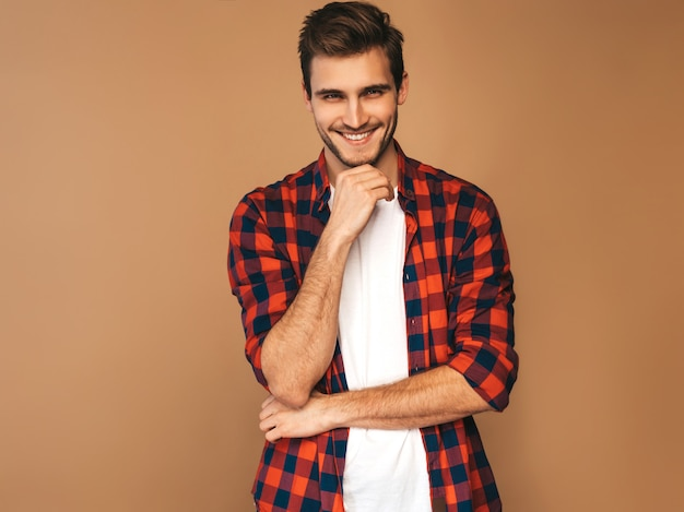 Portrait of handsome smiling stylish young man model dressed in red checkered shirt. fashion man posing. touching his chin Free Photo