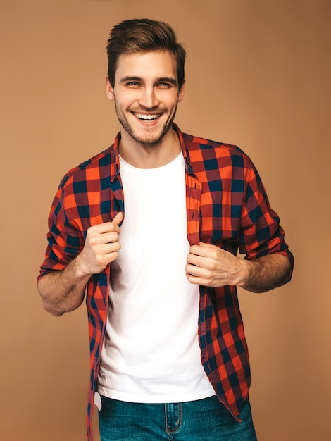 Portrait of handsome smiling stylish young man model dressed in red checkered shirt. fashion man posing Free Photo