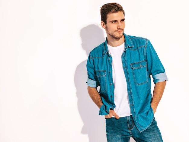 Il ritratto dei jeans d'uso d'uso di modello alla moda sorridenti bei del giovane copre. uomo di moda Foto Gratuite