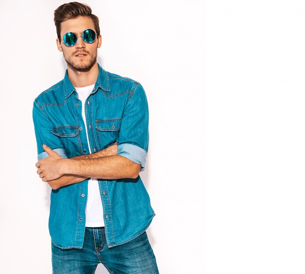 Portrait of handsome smiling stylish young man model wearing jeans clothes and sunglasses. fashion man .crossed arms Free Photo