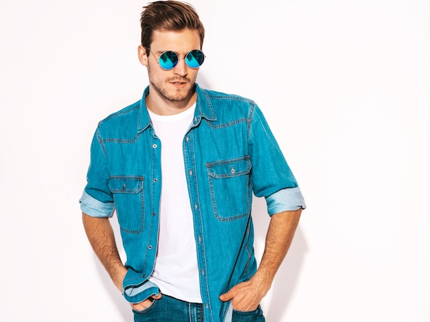 Portrait of handsome smiling stylish young man model wearing jeans clothes and sunglasses. fashion man Free Photo