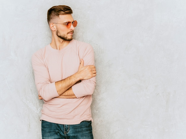 Portrait of handsome smiling young man model wearing casual summer pink clothes. fashion stylish man posing in round sunglasses Free Photo