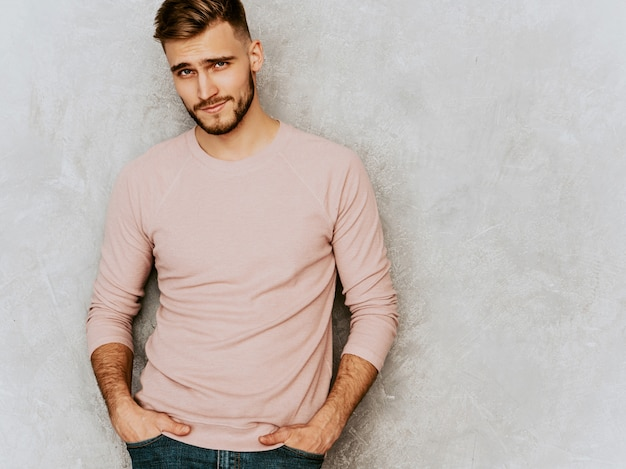 Portrait of handsome smiling young man model wearing casual summer pink clothes. fashion stylish man posing Free Photo