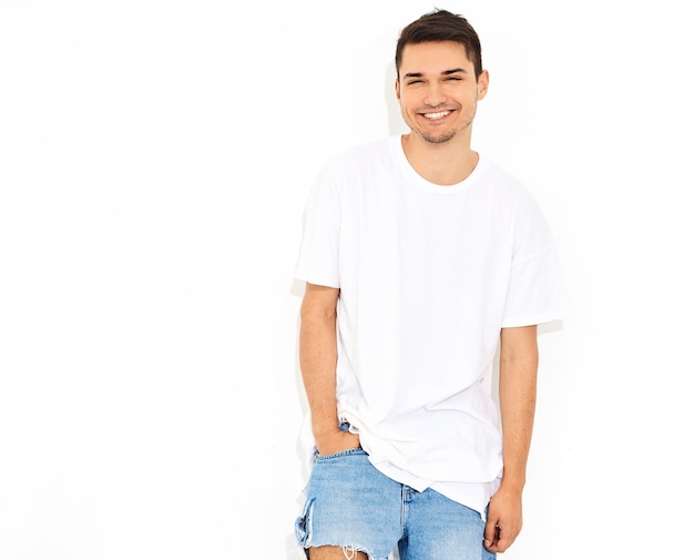 Portrait of handsome smiling young model man dressed in jeans clothes  and t-shirt posing. touching his head Free Photo