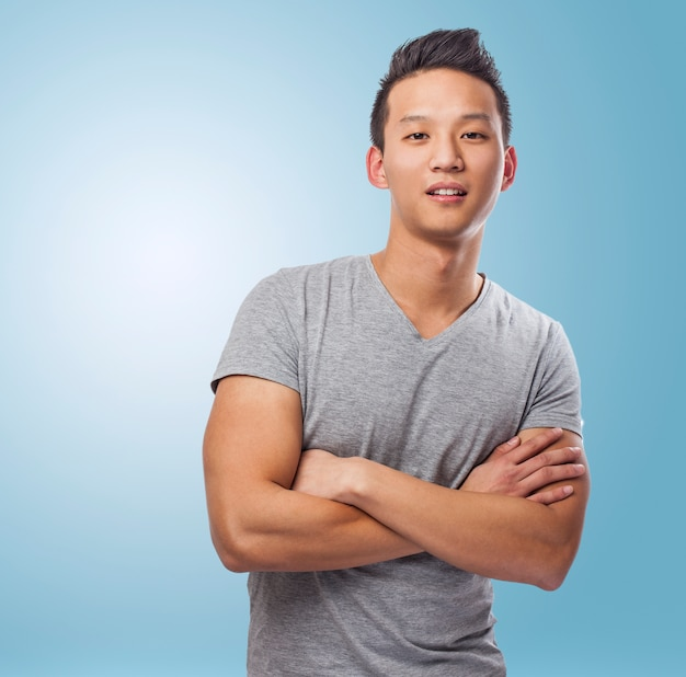 Portrait of handsome young asian man standing over blue backgrou Free Photo
