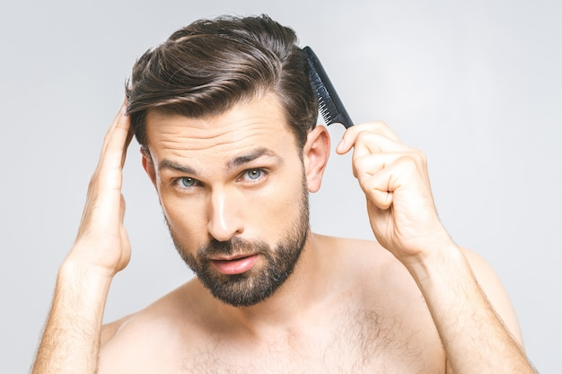 Premium Photo   Portrait of handsome young man combing his hair in  bathroom. isolated over grey background.