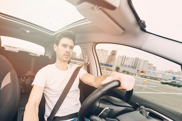 Portrait of handsome young man driving a car Free Photo