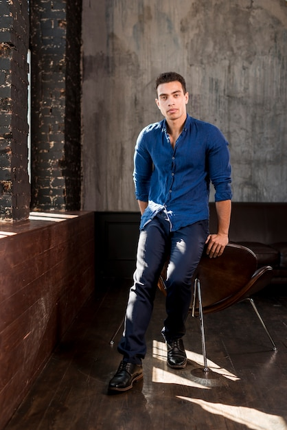 Portrait of a handsome young man leaning on chair in a room Free Photo