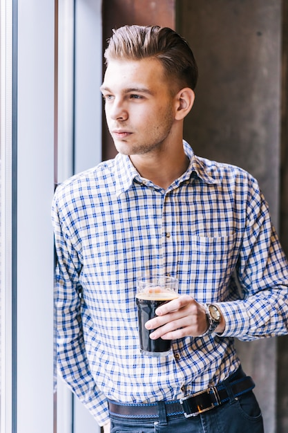 Portrait of a handsome young man leaning at window holding the beer glass Free Photo