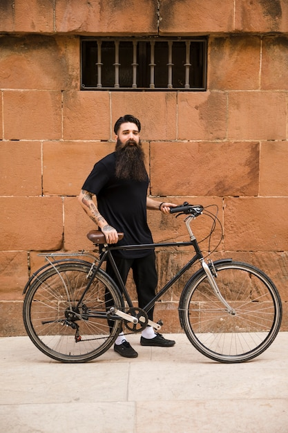 Portrait of a handsome young man standing with his bicycle in front of wall Free Photo