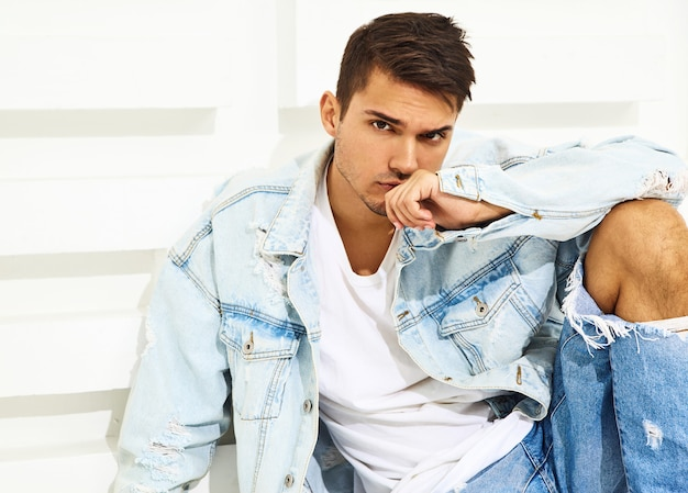 Portrait of handsome young model man dressed in jeans clothes sitting near white textured wall Free Photo